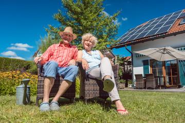 Glückliche Frau und Mann, ein Senioren Paar, entspannt im Garten vor dem Haus