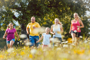 Familie beim Jogging über eine Wiese mit Blumen im Sommer als Sport