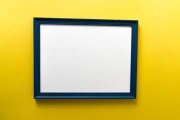 Blue empty picture frame on yellow wall background