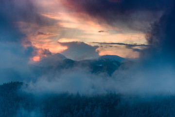 Landscape of dramatic sunset in the winter mountain. Wooded hills covered with snow, fog rising from valleys, colorful cloudy sky - this is impressive picture.
