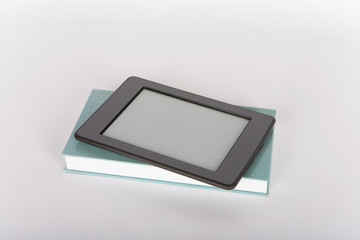 Ebook reader tablet with empty screen on top of a paper book