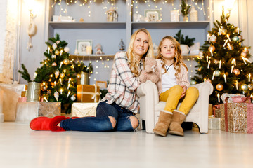 Festive picture of mother hugging daughter sitting on chair