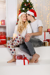 Picture of couple in love with Santa caps and pajamas