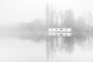 Desolate houseboat in the fogg on the ringvaart in Amsterdam,.