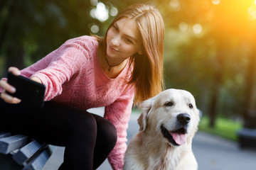 Image of woman on bench making selfie with dog in summer park.