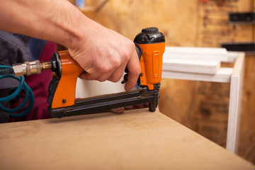 carpenter uses a professional stapler or nail gun