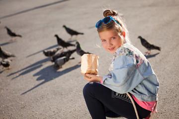 Adorable little girl feeding pigeons outdoors