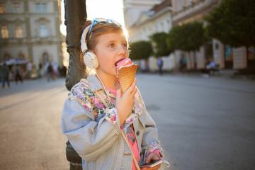 little girl  listening  music on  street and eating ice cream