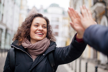 Positive girl giving high five on the street. Glad to see you.