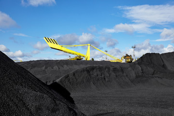 Heap of coal and excavator in coal mine