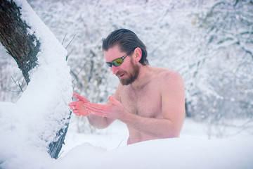 Naked wild man with sunglasses at winter snowy forest