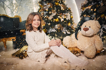 a little girl in beautiful winter clothes and shoes sitting in a beautiful room decorated with New Year's decor and considering gifts for Christmas with the effect of snow