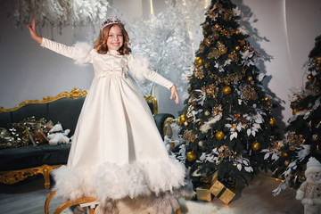 a girl dressed in the image of a snow queen posing in an atmospheric New Year's room with a beautiful Christmas tree, toys and dressed in a white long dress and a silver crown