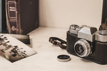 Vintage photo camera in brown retro leather case holder on wooden background with instagram retro filter effect
