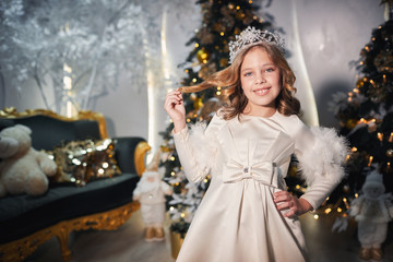 a little girl in a silver crown and in a ballroom white dress sitting on a magnificent green sofa near the Christmas tree, toys, garlands and festive curbs in the New Year atmosphere
