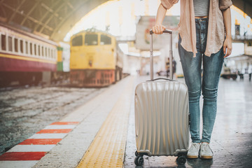 Woman traveler tourist standing with luggage at train station. Active and travel lifestyle concept
