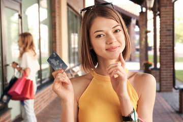Beautiful woman with credit card shopping in strip mall