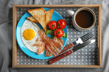Plate with fried egg, bacon and tomatoes on tray