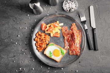 Plate with fried egg, bacon and beans on table