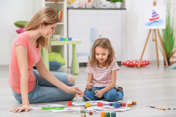 Mother with daughter painting while sitting on floor at home