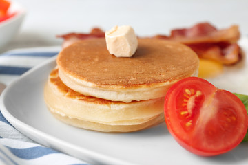 Tasty breakfast with pancakes and tomato on plate