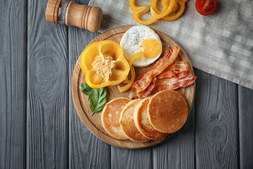 Tasty breakfast with pancakes and bacon on wooden board