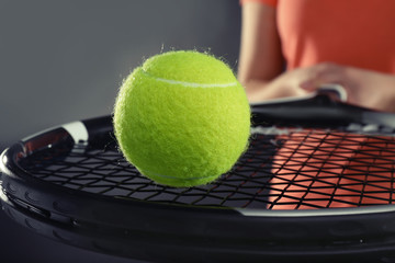 Woman with tennis racket and ball on dark grey background, closeup
