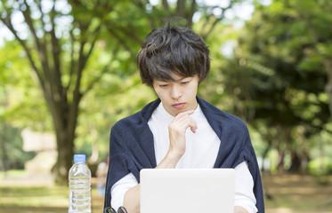 公園でパソコンを操作する男性