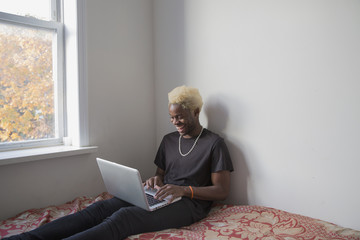 Young man uses his laptop by the window in his apartment