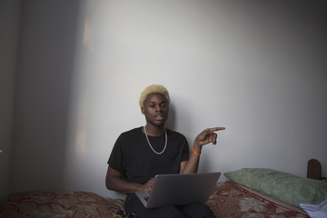 Young man on his laptop in his apartment