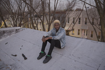 Portrait of a young man sitting on his rooftop