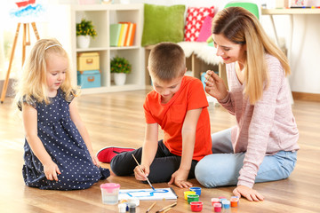 Mother with cute children painting picture, indoors