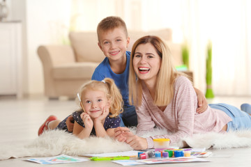 Mother with cute children painting, indoors