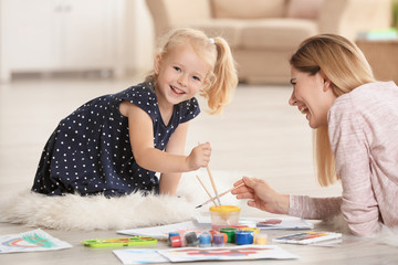 Mother with cute girl painting picture on sheet of paper, indoors