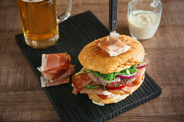 Tasty burger with prosciutto on wooden board