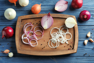Composition with different onions on wooden table