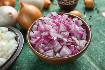 Bowl with cut onion on wooden table