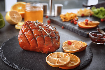 Slate plate with traditional honey baked ham on table