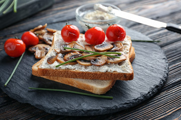 Slate plate with tasty toasts, cheese and vegetables on table