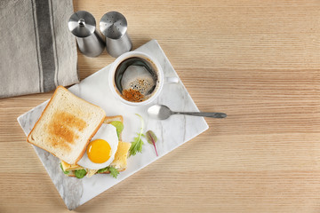 Board with delicious toasts and fried egg on table