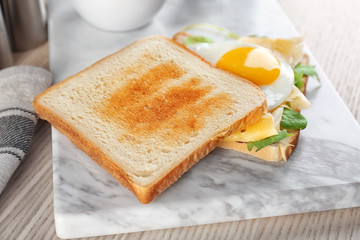 Delicious toasts with fried egg on board, closeup