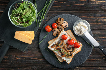 Composition with toasts, cheese, tomatoes and mushrooms on table