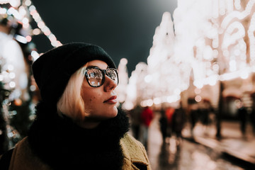 Modern pretty woman in glasses reflected city lights. Close up portrait