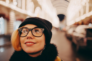 Modern pretty woman is smiling in glasses reflected city lights. Close up portrait