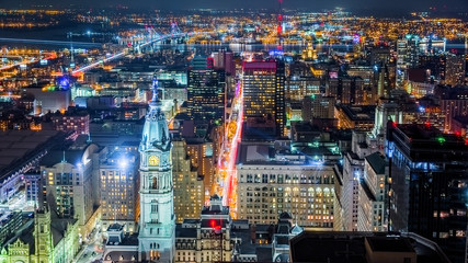 Fotomurales - Aerial Philadelphia cityscape by night with the City Hall tower in the foreground and Ben Franklin bridge spanning Delaware river in the back