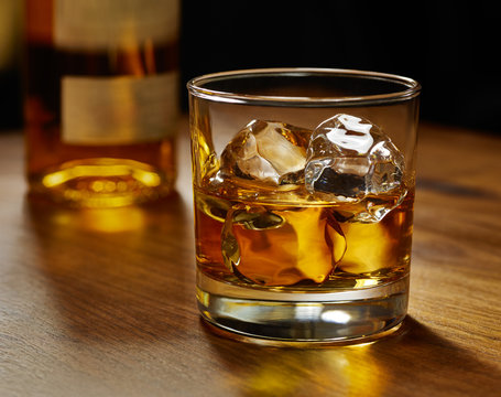 Glass of whiskey on ice with bottle on wood bar