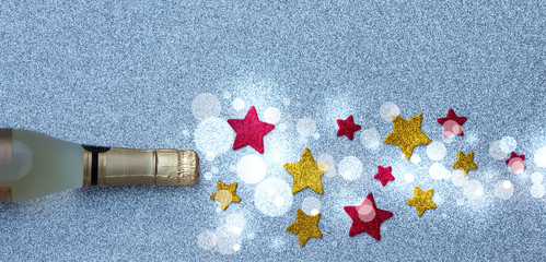 Spray of the stars from a bottle of champagne on a silver background. Christmas and New Year's decor.