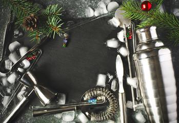 Set of bar tools and ingredients for making a cocktails arranged on a stone background with black board for copy space. Christmas concept