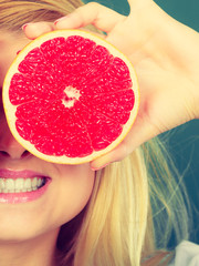 Woman holding fruit red grapefruit half