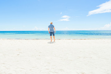 Casual man in hat standing on the beach. Back view.